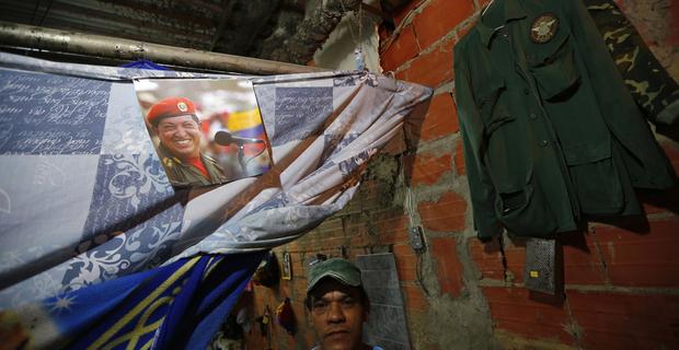 caption:Uno degli abitanti di Torre de David posa sulla soglia del suo appartamento sotto alla foto del ex presidente Hugo Chavez. © REUTERS/Jorge Silva