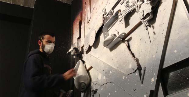 caption: Artur Bordalo all'opera nel creare un murale 3D costituito da una base lignea su cui è installato un collage di immondizia, pneumatici e cavi. Foto dalla pagina Facebook dell'artista.